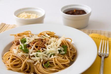 Close-up beeld van een bord met spaghetti, tomaten pesto, peterselie en Parmezaanse kaas.