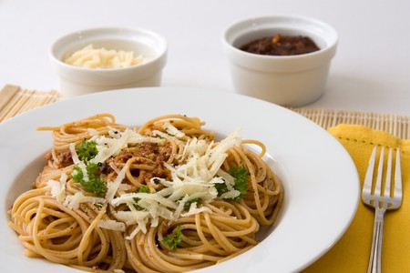 Closeup image of a plate with spaghetti, tomato pesto, parsley and parmesan.