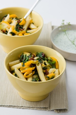 Pasta salad with fried zucchini and spinach and a dip made from yogurt and herbs. Stock Photo