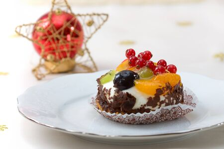 Christmas decorated table with a piece of a fancy fruit cake. photo