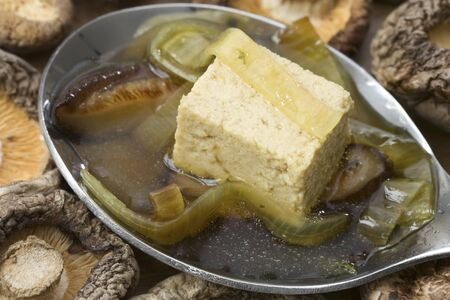 Spoon with Japanese vegetarian broth made from mushrooms, tofu and leek photo