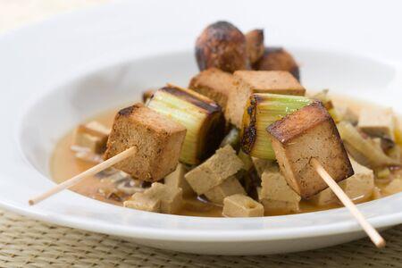 Asian vegetarian skewers made from mushrooms, tofu and leek, served on vegetables. photo