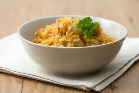 Traditional vegetarian Indian dish called Dal which is made from red lentils with an apple.