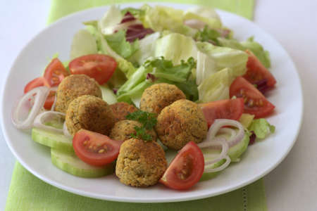 White plate with falafel, cucumbers, tomatoes and salad. photo