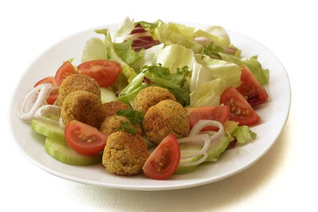 falafel: White plate with falafel, cucumbers, tomatoes and salad.