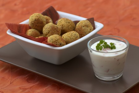Bowl with falafel which are vegetarian and made from chickpeas together with some yoghurt dip.