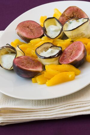Plate with vegetarian fingerfood with marinated figs made from aubergines, cream cheese and yellow bell pepper. photo