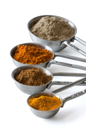 spice isolated: Measuring spoons with spices like curcuma, cardamom, cinnamon and red pepper isolated on white background. Stock Photo