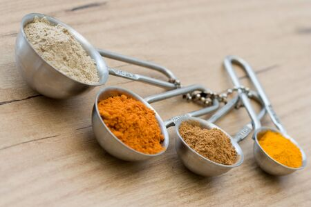 cardamum: Measuring spoons with spices like curcuma, cardamom, cinnamon and red pepper. Stock Photo