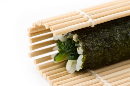 Close-up image of the bamboo rolling mat while preparing hosomaki sushi made from spinach. Stock Photo