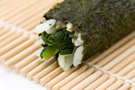 Close-up image of the bamboo rolling mat while preparing hosomaki sushi made from spinach. photo