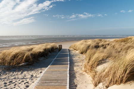 Path to the beach on Langeoog through the dunes with the North Sea in the background photo