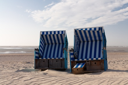 Two beach chairs in blue white with the North Sea in the background. Stock Photo