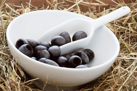 Black olives, served in a bowl placed on straw. photo