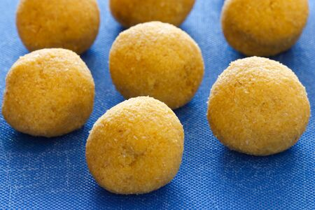 Close-up image of raw chick peas balls on a blue countertop which shows the making of falafels. photo
