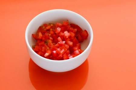 White bowl with chopped tomatoes and an orange background.