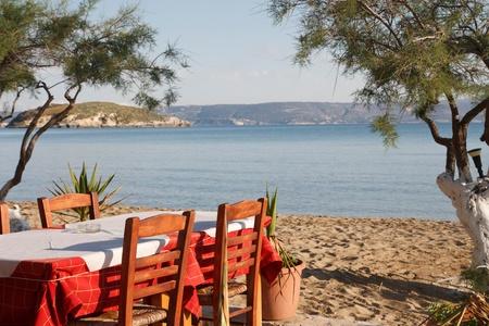 Tafel en stoelen van een Griekse taverna aan het strand.