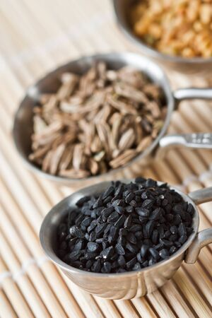 Close up image of measuring spoons with black cumin seeds. photo