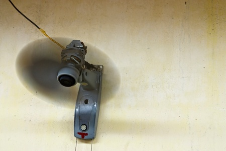 Rotating fan on an old yellow wall with copy space. photo