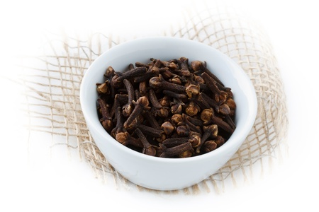 Small bowl with cloves and a white background.