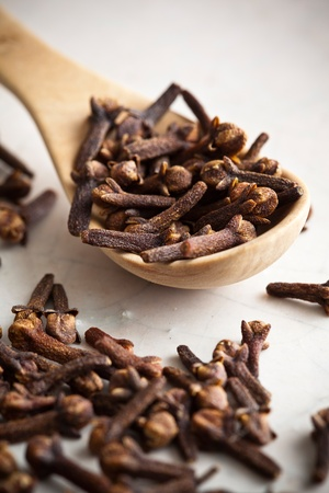 clove: Cloves and a wooden spoon on stone. Stock Photo