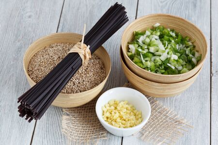 Ingredients for an Asian dish: rice noodles, spring onions, sesame and ginger.