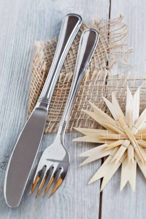 menue: Silverware which is decorated for Christmas with a straw star on a white wooden background. Stock Photo