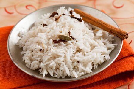 Image of Indian rice with spices like cloves, cinnamon and cardamom served on an orange napkin. Stock Photo - 10574154