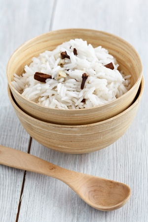 Image of Indian rice with spices like cloves, cinnamon and cardamom, served on a white wooden background. Stock Photo - 10574149