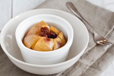 Gebakken appel met rozijnen geserveerd op een bruine servet.