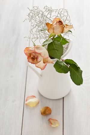 Bunch of dried rosed in a jar on a white wooden background. photo