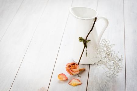 Jar met een gedroogde roos op een witte houten achtergrond. Stockfoto