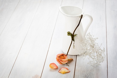 Jar with a dried rose on a white wooden background. photo