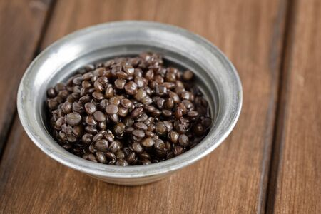 Small silver bowl with cooked black lentils on a wooden board. photo