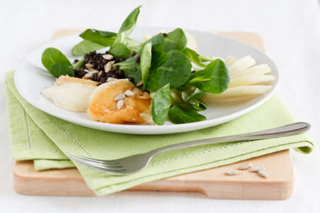 Valerianella with fried halloumi cheese, pears and black lentils, served on a plate with a green napkin. photo