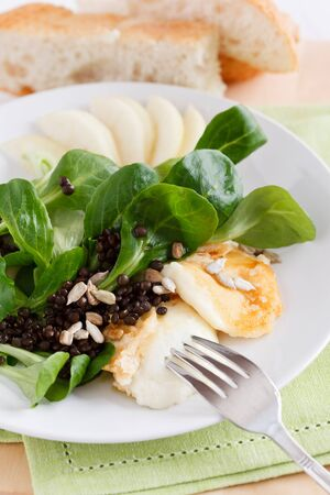 Valerianella with fried halloumi cheese, pears and black lentils, served with flatbread. photo