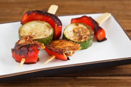 Close-up image of fried vegetable skewers with red bell pepper, zucchini and halloumi cheese on a wooden background. photo