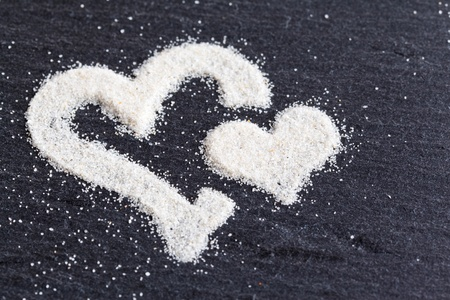 Hearte which are made from sand on a stone background. Stock Photo