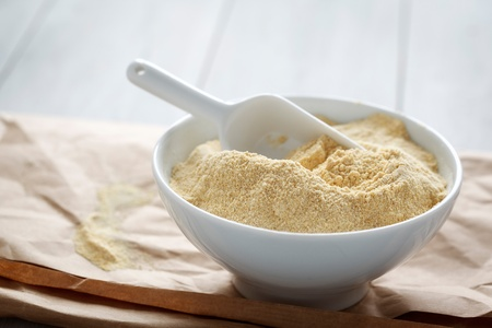 Bowl with chickpea flour on a paper. Stock Photo