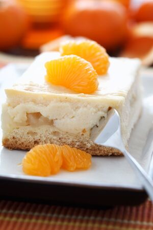 cheese cake: Close-up image of a piece cheese cake with mandarins and a fork.