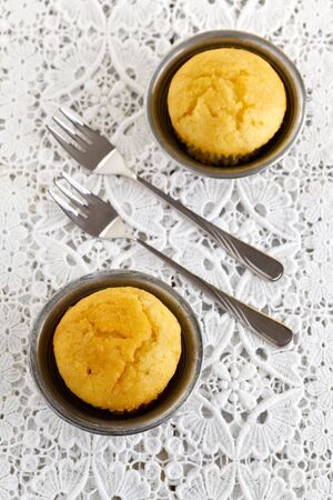 doiley: Top view of two muffins, served on a doily.