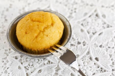 doiley: Lemon muffin with a pasty fork served on a doily.
