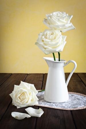 Mok met rozen op een kleedje op een houten achtergrond.