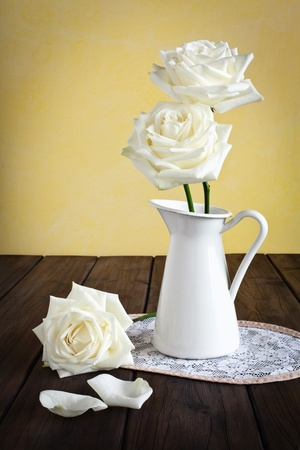 Mug with roses on a doily placed on a wooden background.