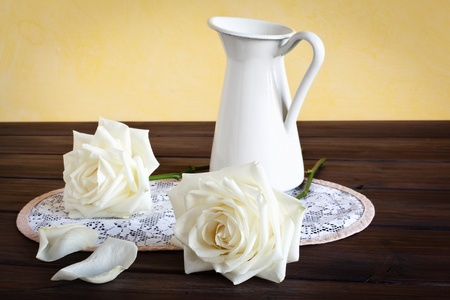 Still life with white roses, a mug and a doily placed on a wooden background.