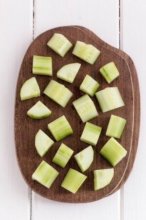 Cucumber slices on a brown cutting board