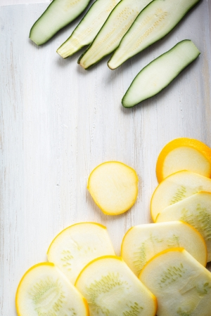 cocozelle: Yellow and green zucchini slices on a white wooden background. Stock Photo