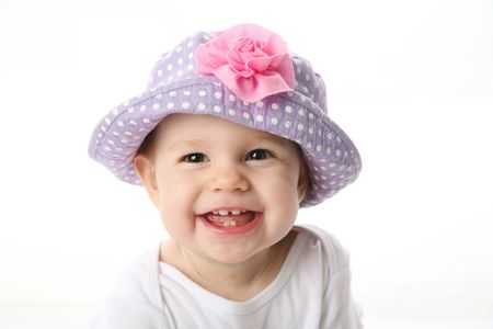 Smiling baby girl showing teeth wearing a purple polka dot hat with pink flower isolated on white background Standard-Bild