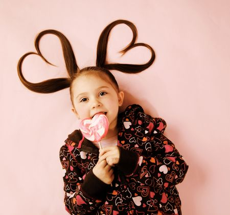 Young girl licking Valentines heart lollipop with pigtails photo