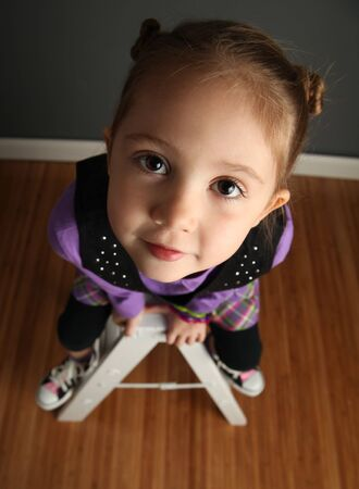 Young girl sitting on a ladder, shot from above Stock Photo - 8046090